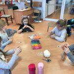 Uczniowie siedzą przy stoliku i szydełkują