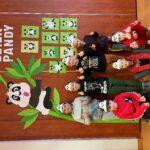 Siedmioro dzieci w opaskach z wizerunkiem pand stoi na tle dekoracji ściennych: wielki zielony bambus z uwieszoną na nim pandą. Obok powieszone są również prace plastyczne dzieci
