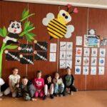 Grupka dzieci kuca pod ścianą, na której przeywieszone są ich prace dotyczące kosmosu