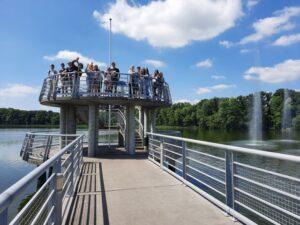 Uczniowie stoją na wysokiej, okrągłej platformie na molo, nad Jeziorem Kórnickim, obok widać fontannę