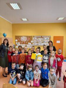 Na fotografii Emilia, laureatka konkursu otoczona jest z uczniami klasy 1b , Panią Dyrektor Małgorzatą Szomek i wychowawcą klasy Panią Eweliną Wdowiak. Emilia cieszy się z wygranej i otrzymanego prezentu.