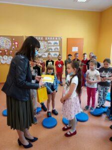 Dyrektor Szkoły Pani Małgorzata Szomek ubrana w sukienkę w oliwkowy kolor wręcza zwyciężczyni wygrany tablet oraz Dyplom. Dziewczynka i pozostali uczniowie z uwagą wsłuchują się w słowa. Emilia stoi bokiem do pozostałych rówieśników, a długie, ciemne włosów sięgają do pasa.