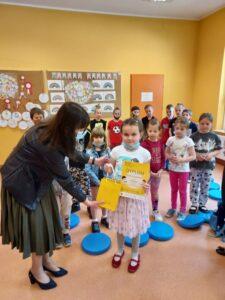 Emilia, laureatka na tle klasy odbiera wygraną nagrodę z rąk Pani Dyrektor Małgorzaty Szomek. Pani Dyrektor wręcza dziewczynce Dyplom zajęcia 1 miejsca oraz torebkę z prezentem.