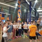 Uczniowie w strojach sportowych słuchają instruktorów Stacji Grawitacja