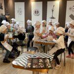 Dzieci ubrane w białe fartuchy i czapki kucharskie siedzą przy stolikach  w Muzeum Czekolady, degustując słodycze