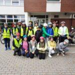 Grupa uczniów w kaskach rowerowych i kamizelkach odblaskowych przed szkoła w Paczkowie