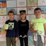 Dzieci z puszką do zbierania pieniędzy stoją przed gazetką ścienną