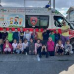Dzieci stoją przed kolorowym ambulansem